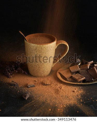 Hot chocolate with chocolate slices and chocolate powder on a dark background - stock photo