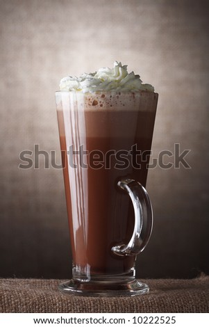 Hot Chocolate with cream in Tall Glass on brown rustic background, Low Key  Lighting Technique - stock photo