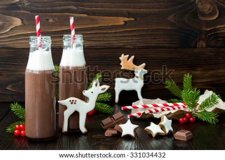 Hot chocolate with whipped cream in old-fashioned retro bottles with red striped straws. Christmas holiday drink and gingerbread baby deer or fawn cookies. Free text copy space - stock photo