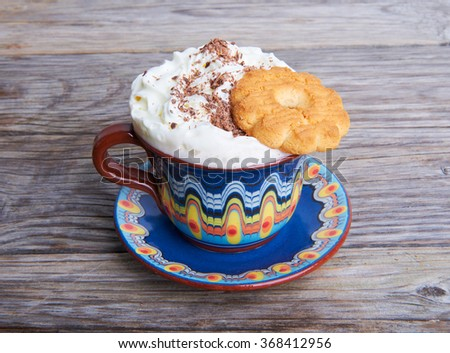 Hot cocoa drink cappuccino with whipped cream and shortbread on a wooden background - stock photo