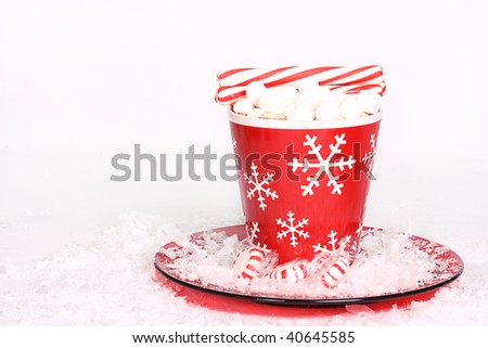 Hot cocoa in a red snowflake mug with peppermint sticks and peppermints - stock photo