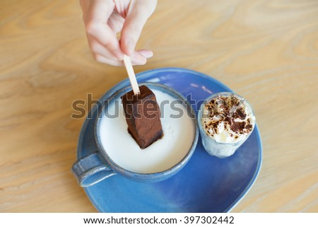 Hot cocoa served with hot milk , cocoa stick and a glass of whipped cream on a blue plate. - stock photo