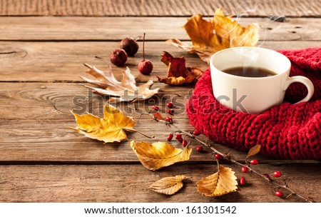 Hot coffee and autumn leaves on vintage wood background - seasonal relax concept - stock photo