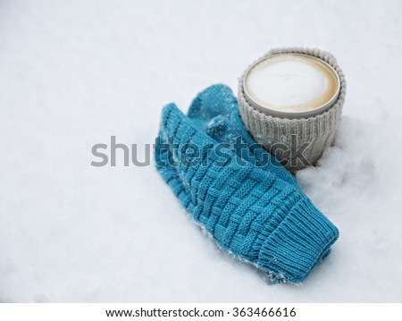 hot coffee and blue gloves on the snow - stock photo