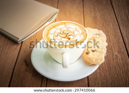 Hot coffee and cookie on saucer with  note book on wooden background - stock photo