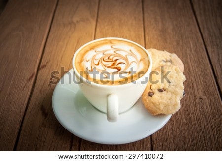 Hot coffee and cookie on saucer with wooden background - stock photo