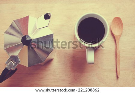 Hot coffee and moka pot with wooden spoon, retro filter effect - stock photo