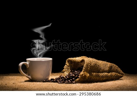 Hot coffee and Roasted coffee bean in bag on black background. - stock photo