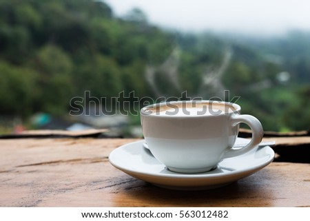 Hot coffee cappuccino cup with milk foam on wood table background.