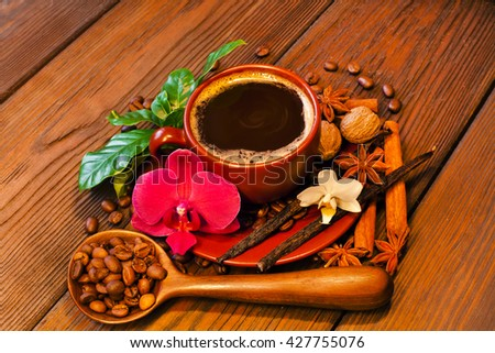 Hot coffee cup and coffee beans with spices and orchid flowers on a wooden table  - stock photo
