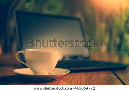 hot coffee cup and laptop on wood table, in morning