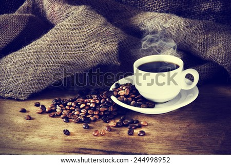 Hot Coffee cup and roast coffee beans on a wooden table. Dark background, Vintage color tone - stock photo