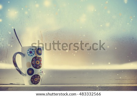 Hot Coffee cup on a frosty winter day window background/ Christmas holidays background/ Winter cozy background