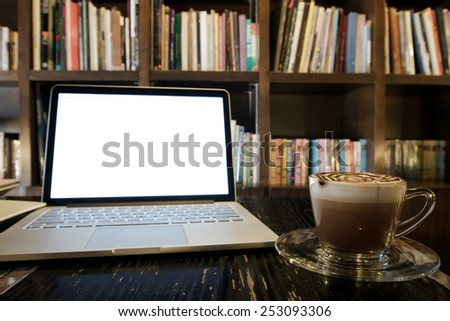 Hot coffee cup on a table laptop in library - stock photo
