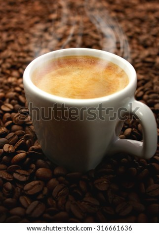 Hot coffee cup on coffee beans - stock photo