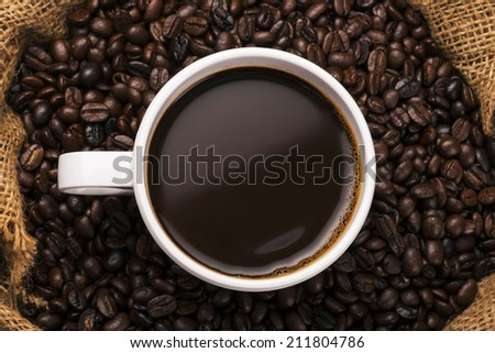 Hot Coffee Cup on Coffee Beans in Bag - stock photo