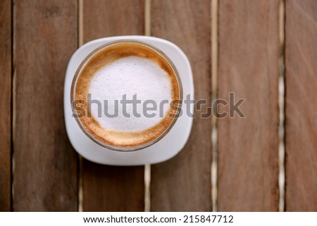 Hot coffee cup on wood table top view