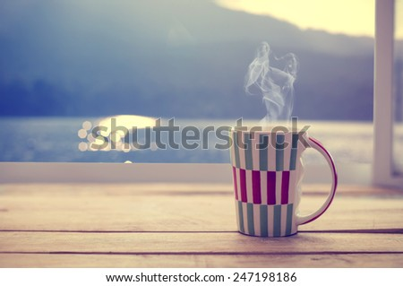 Hot coffee cup on wood table with raindrop window, summer time (vintage color tone) - stock photo