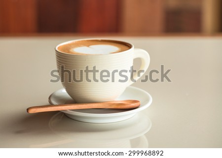 Hot coffee cup with white heart  on white desk on wooden wall - stock photo