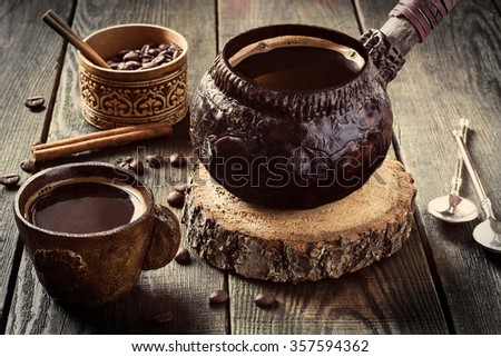 Hot coffee in clay crockery on a wooden table, vintage style. Selective focus, toned photo  - stock photo