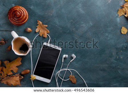 Hot coffee in mug and bun, white mobile phone with headphones, autumn leaf on a vintage table surface, selective focus