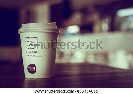 Hot coffee in paper cup with check list of coffee type  place on table