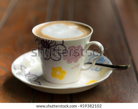 Hot coffee in the white ceramic cup on the table. - stock photo