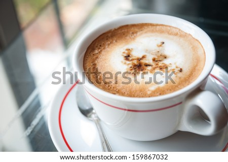 Hot coffee is on the glass table - stock photo