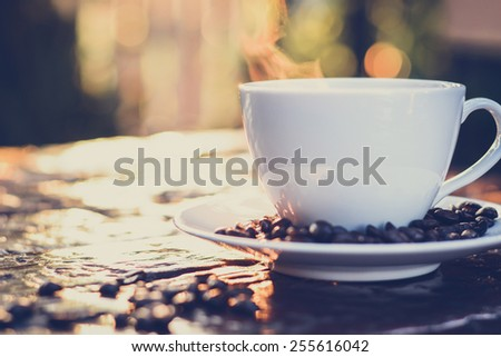 Hot coffee on old wood table with dark blur bokeh background  - vintage style colors with soft focus - stock photo