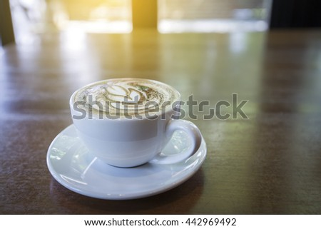 Hot coffee on the table with coffee shop background - stock photo