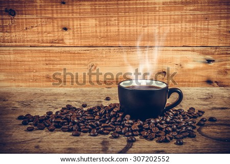 Hot coffee on wooden background, vintage style - stock photo