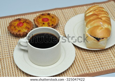 hot coffee with coconut tart and  bread with berry on bamboo mat
