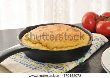Hot cornbread in a cast iron skillet cooling by the window - stock photo