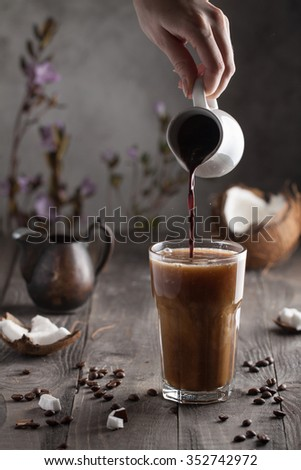 Hot creamy coffee with liquid chocolate in motion in a glass - stock photo
