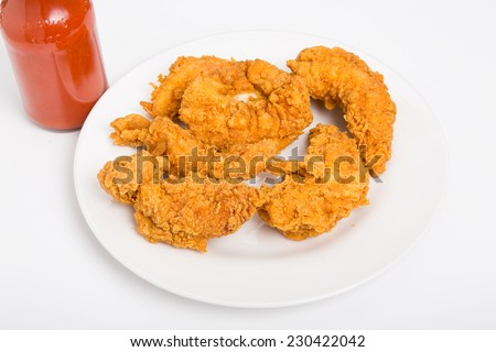 Hot, crispy chicken strips on a white plate with hot sauce - stock photo