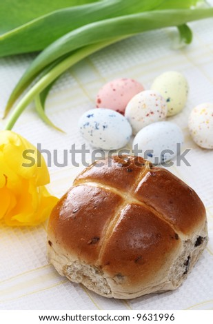 hot cross bun, Speckled easter eggs and yellow tulip on background - stock photo