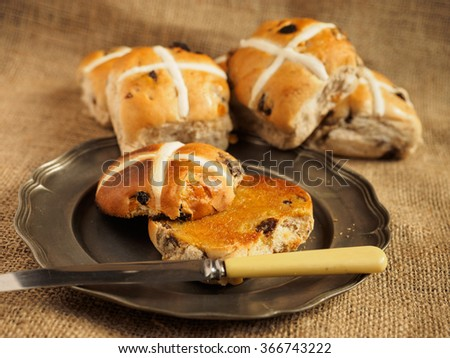 Hot cross buns on a rustic background. One of the buns has been toasted and buttered. - stock photo