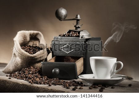 hot cup of coffee with coffee grinder and coffee beans in jute bag on wooden table - stock photo