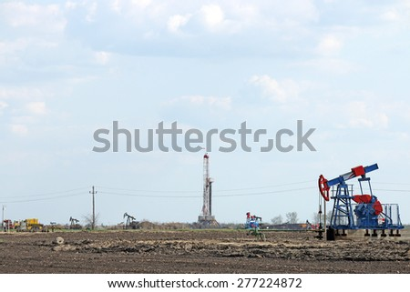 hot day on oilfield with pump jacks and drilling rig - stock photo