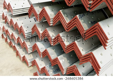 Hot-dip steel angles bunch on the rack in warehouse before shipment  - stock photo