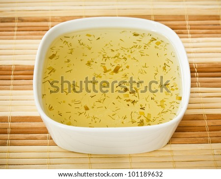 Hot Dish of Chicken Broth with Sliced Dill on a bamboo mat - stock photo