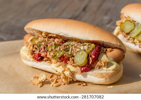 Hot Dog sausage in a bun with roasted onions, pickles, ketchup and mustard on rustic wooden background - stock photo