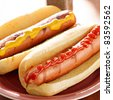 hot dog- two on a plate with ketchup and mustard. - stock photo