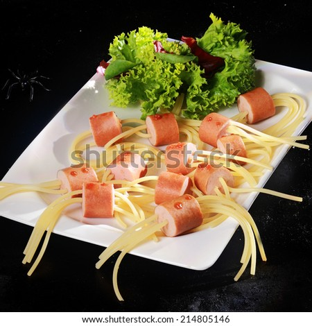 Hot Dog Wiener and Noodle Halloween Spider Snacks with Lettuce Garnish on White Plate on Black Background - stock photo