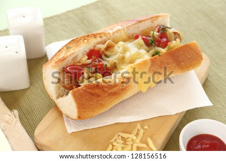 Hot dog with melted cheddar cheese with onion and ketchup. - stock photo