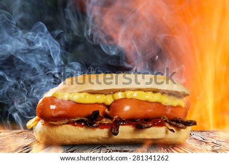 Hot dog with mustard and ketchup on wooden table with fire flames background. - stock photo