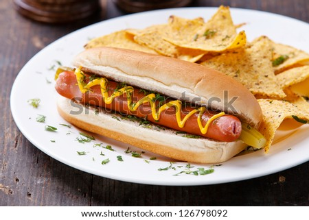 Hot dog with mustard and potato chips on wooden background - stock photo