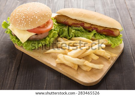 Hot dogs, hamburgers and french fries on the wooden background. - stock photo