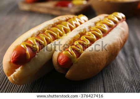 Hot dogs on wooden background closeup - stock photo
