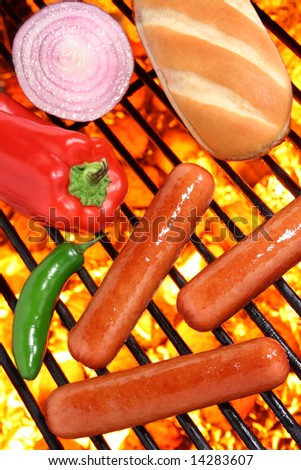 Hot dogs, peppers, onion and bun on a hot barbecue grill - stock photo